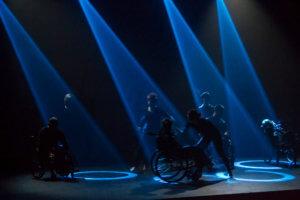 Ciemna scena, doświetlona czteroma niebieskimi reflektorami, które na podłodze tworzą cztery niebieskie okręgi.Pomiędzy tymi okręgami porusza się ośmiu tancerzy, w tym czterech na wózkach inwalidzkich. W pierwszym planie duet osoby pełnosprawnej z osobą na wózku inwalidzkim, są oni ustawieni bokiem do widowni. Tancerze są ubrani na czarno.