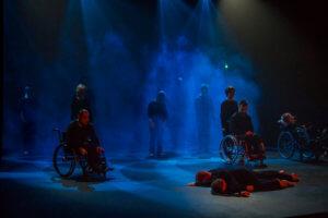 Scena oświetlona na niebiesko, w tle unosi się dym. Na pierwszym planie sceny dwóch tancerzy leży bokiem do widowni. Za nimi w odstępach przodem do widowni znajdują trzy osoby siedzące na wózkach inwalidzkich a za nimi kolejne sześć osób. Wszyscy stoją nieruchomo, wzrok skierowany w stronę widowni. Wszyscy są ubrani na czarno.