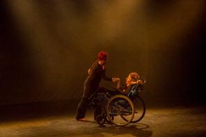 Scena doświetlona pomarańczowo-żółtym światłem. Na scenie znajdują się na przeciw siebie, dwie tancerki, ubrane na czarno.Tancerka po lewej stronie ma rude włosy, stoi delikatnie pochylona do przodu, lewa reka jest lekko odchylona do tyłu, prawa skierowana do lewej ręki drugiej tancerki, znajdujacej się na przeciw, po prawej stronie na scenie. Tancerka siedzi na wózku inwalidzkim w pozycji półleżącej.