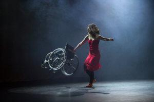 Tancerka z długimi włosami, ubrana w czarne getry oraz zwiewną czerwoną sukienkę na ramiączkach znajduje się na scenie, jest doświetlona białym światłem w tle delikatnie unosi się dym. Tancerka wykonuje piruet w lewą stronę. Wsparta jest na lewej nodze, prawa jest delikatnie uniesiona robiąc krok w przód. W prawej ręce tancerka trzyma uniesiony wózek inwalidzki i wykonuje nim zamaszysty ruch w prawą stronę, natomiast lewa ręka jest uniesiona równo z ramieniem.