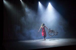 Scena doświetlona czterema białymi reflektorami, które tworzą na scenie jasne koło, w którm unosi się dym. W środku jasnego koła znajduje się tancerka obrócona tyłem, ubarana w czarne getry oraz zwiewną czerwoną sukienkę na ramiączkach. W prawej ręce tancerka trzyma uniesiony w górę, na poziomie bioder wózek inwalidzki. Lewa ręka tancerki jest również uniesiona, prawa stopa jest lekko uniesiona.