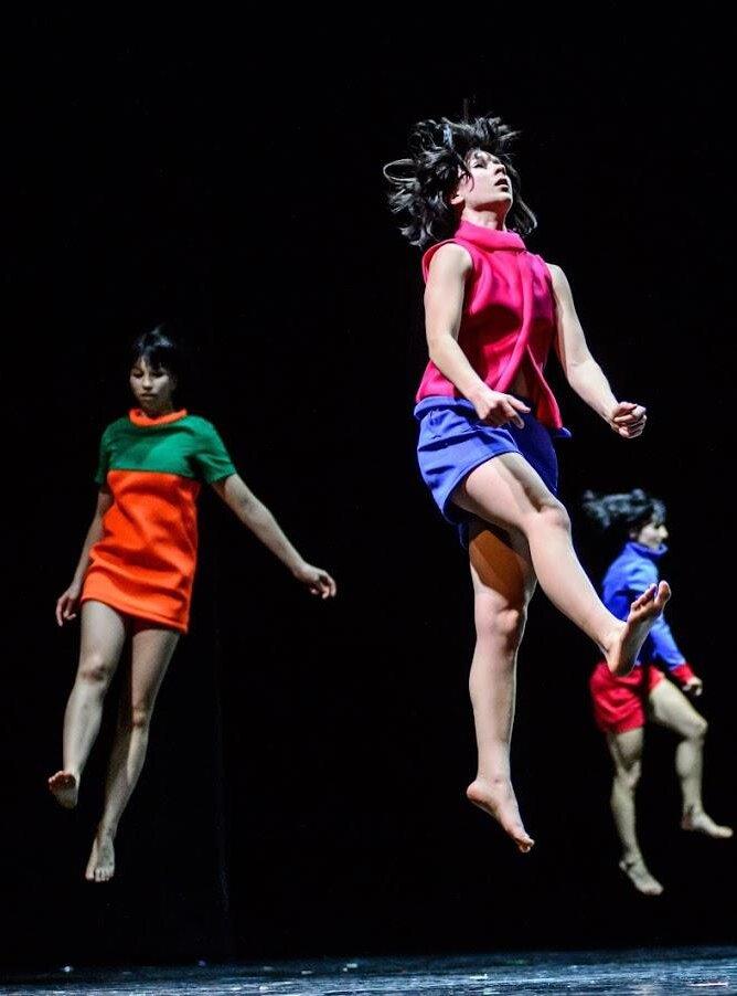 Zdjęcie ze spektaklu Olsztyńskiego Teatru Tańca Pan Kejk. Na zdjęciu znajudują się trzy tancerki skaczące w górę. Na pierwszym planie tancerka ubrana w różową bluzkę bez rękawów i granatowe szorty. Po jej lewej stronie tancerka ubrana wgranatową bluzkę i różowe szort. Po prawej stronie tancerka w zielono-pomarańczowej krótkiej sukience.