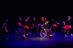 Scena doświetlona niebiesko-czerwonym światłem. Znajduje się na niej trzynastu tancerzy, w tym czterech poruszających się na wózkach inwalidzkich. Tancerki są ubrane w czarne bluzki z długim rękawem i czarne getry, do tego mają spódniczki z cienkiego delikatnego materiału w kolorze fuksjowym. Tancerze są ubrani w czarne spodnie i czarne bluzy z długim rękawem, przewiązani szarfami z delikatnego cieńkiego materiału w kolorze fuksjowym. Tancerze biegają po scenie.