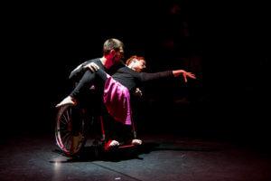 Ciemna scena, na środku białe światło, e którym znajduje się tancerz na wózku inwalidzkim a na jego kolanach znajduje się tancerka, wykonująca figurę taneczną. Ubrani są na czarno, tancerka ma spódnicę w kolorze fuksjowym.