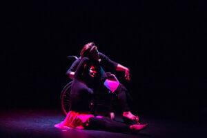 Na zaciemnionej scenie doświetlonej czerwonym światłe są dwie tancerki. Jedna z nich o blond włosach siedzi na scenie z wyprostowanymi nogami. Jej prawa ręka jest zgięta nad głową w lewą stronę. Obok niej znajudeje się druga tancerka, siedząca na wózku inwalidzkim. Jej głowa skierowana jest w prawą stronę, dotyka prawej ręki siedzącej na ziemi tancerki.Obydwie są ubrane w czarne bluzki z długim rękawem i czarne getry, do tego mają spódniczki z cienkiego delikatnego materiału w kolorze fuksjowym.