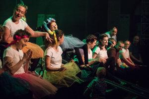 Na proscenium siedzą tancerze. Ubrani w białe koszulki i kolorowe tiulowe spódnice.