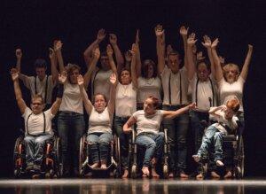 Na scenie znajduje się grupa tancerzy stojących obok siebie w trzech rzędach. Wszyscy tancerze mają uniesione ręce w górę i ubrani są w białe koszulki i spodnie dżinsowe. W pierwszym rzędzie znajdują się cztery osoby na wózkach inwalidzkich.