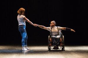 Duet dwóch tancerzy. Tancerz jest na wózku inwalidzkim a tancerka stoi. Trzymają się za ręce. Ubrani w białe koszulki i spodnie dżinsowe.