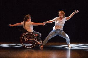 Duet dwóch tancerek, trzymających się za wyprostowane ręce, stojące na przeciw siebie. Tancerki ubrane w białe koszulki i spodnie dżinsowe.