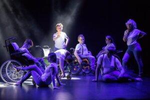 Grupa tancerzy znajduje się na scenie i wykonuje różne figury. Scena jest doświetlona w kolorach niebiesko-białych.